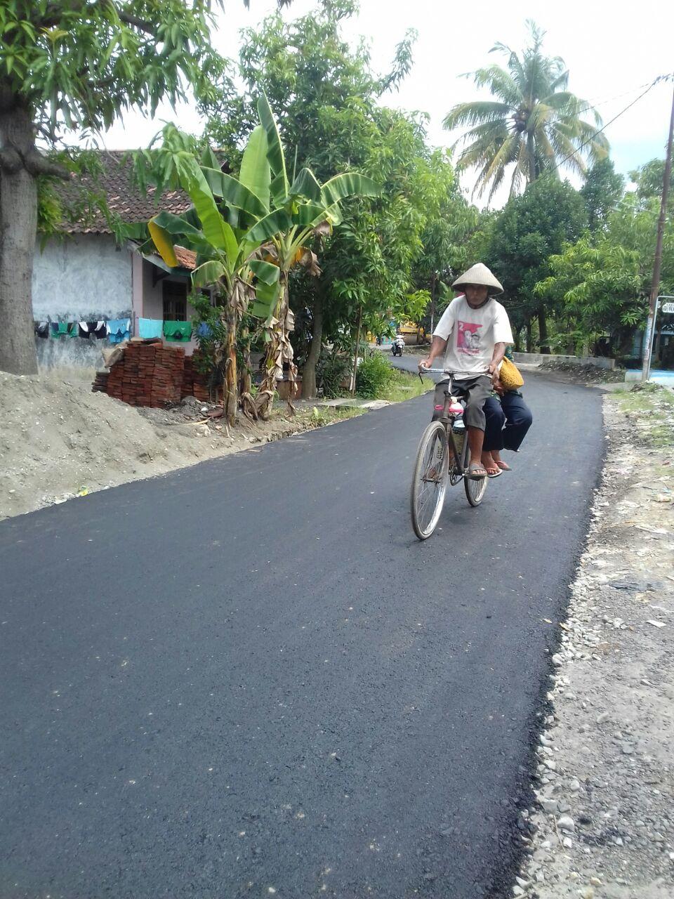 Salah satu warga sedang menikmati jalan aspal baru